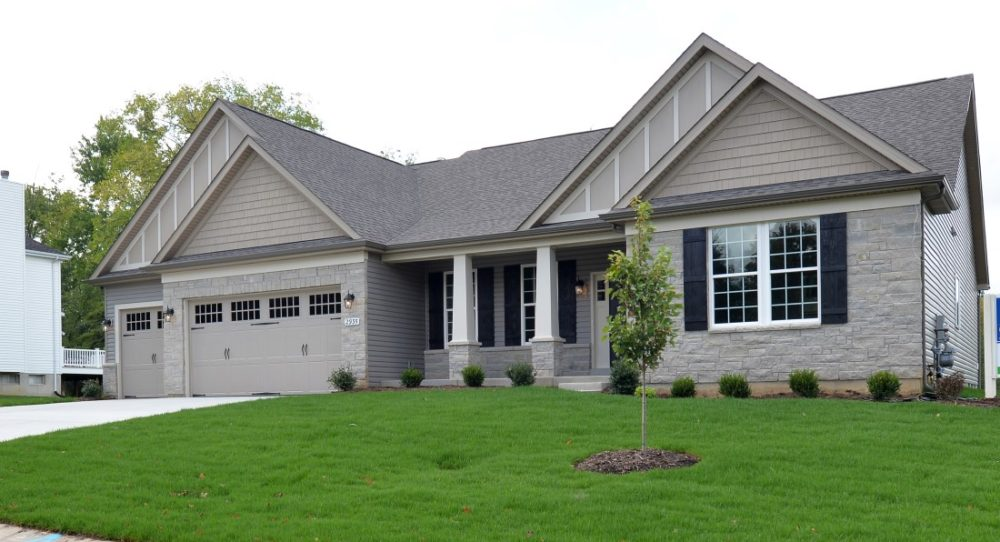 The single-story Monaco has a beautiful stone front with carriage doors on the 3 car garage and columns on the front porch.