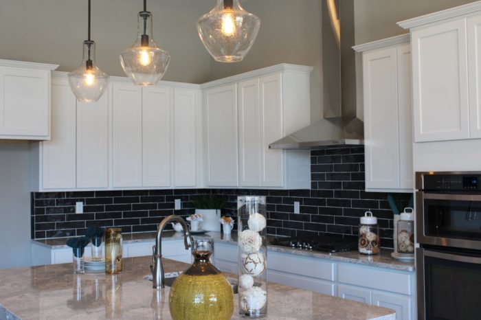 "The Gourmet Kitchen has beautiful black subway tile, 42"" white cabinetry, stainless appliances and an oversized prep island."