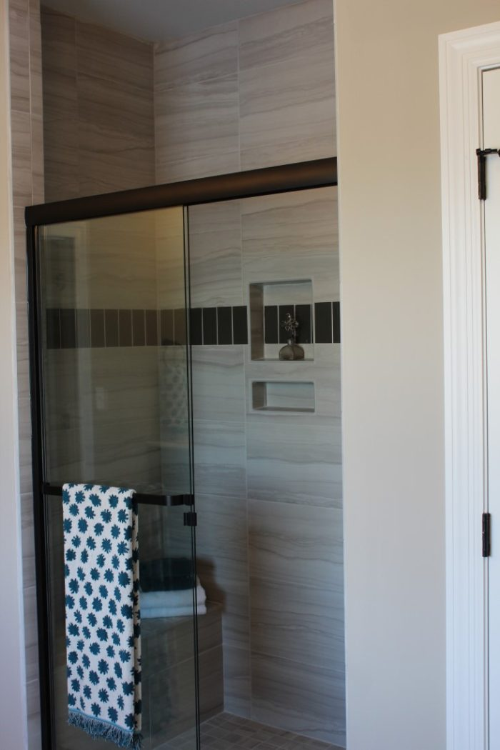 The custom oversize shower has beautiful tile work, a bench, and two storage nooks.